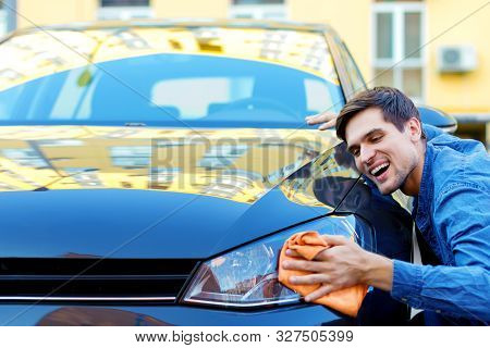 Happy Cheerful Owner Of New Black Car Is Wiping, Cleaning Auto With Orange Rag. Smiling Brunette Man