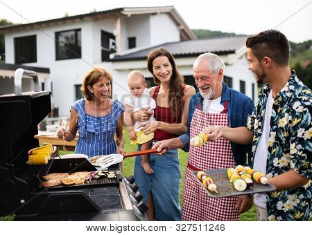 Portrait Of Multigeneration Family Outdoors On Garden Barbecue, Grilling.