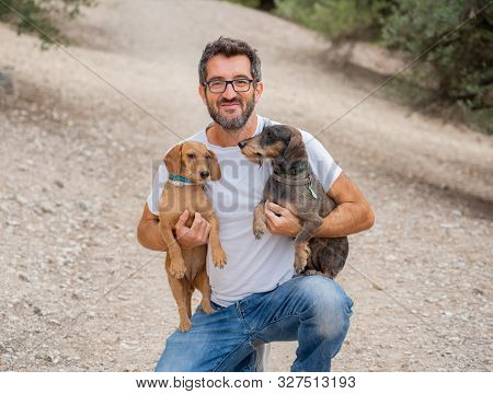 Happy Owner Man With Two Old Cute Dachshund Dog Dogs In The Park
