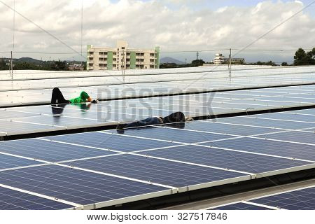 Technicians Arranging Cable Under Pv Modules Of A Solar Rooftop System