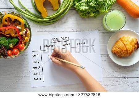 Calories Control, Meal Plan, Food Diet And Weight Loss Concept. Top View Of Hand Filling Meal Plan O