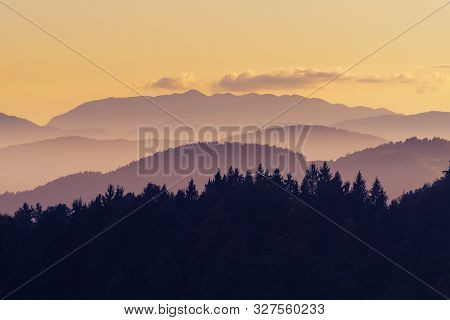 Beautiful Pink And Orange Color Nuances Of Twilight Sky, Hills And Forests After Sunset. Travel, Hik
