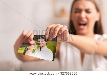 Breakup. Angry Girl Tearing Apart Photo Of Happy Moments With Ex-boyfriend After Quarrel And Seperat