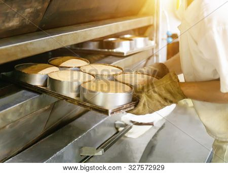 Male Cook Takes Cakes Out Of A Hot Oven For Making Cakes, Industry