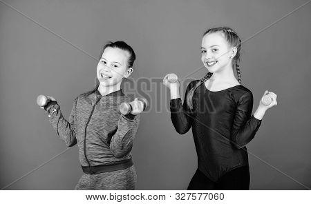 On way to stronger body. Girls exercising with dumbbells. Beginner dumbbells exercises. Children hold dumbbells blue background. Sport for teens. Easy exercises with dumbbell. Sporty upbringing poster