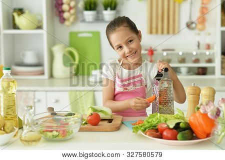 Portrait Of Girl Preparing Delicious Fresh Salad In Kitchen