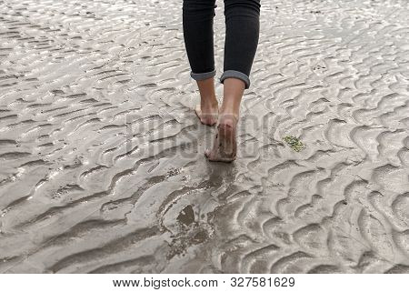 Young Woman Walking And Playing On Sandy Beach And Leaving Footprints In The Beach. Killbrittain, Ki