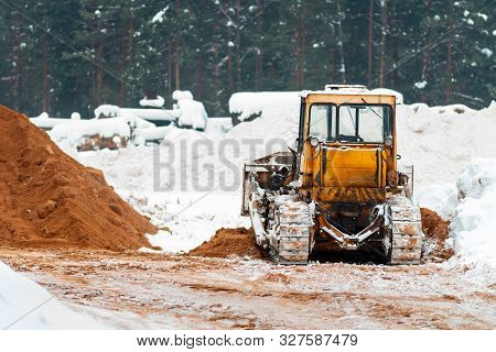 Yellow Caterpillar Tractor. Heavy Tractor, Construction Machinery, Industrial Vehicle. Winter Time