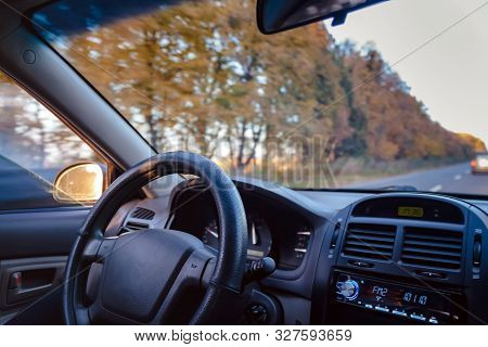 A Man Driving A Car On An Autumn Yellow-orange Road. Close-up Of A Hand