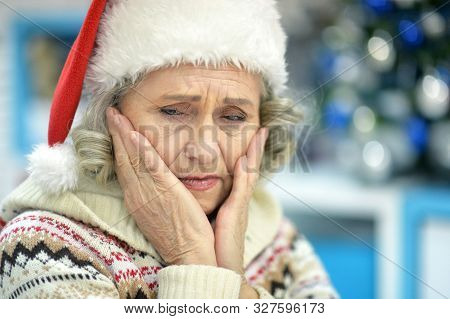 Close Up Portrait Of Sad Senior Woman In Santa Hat