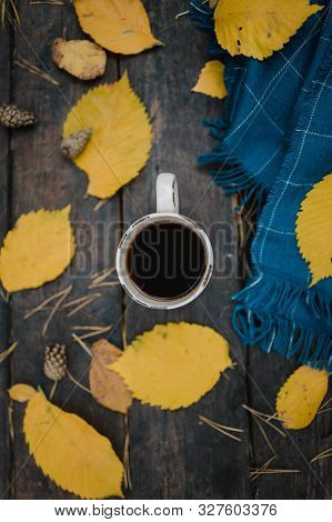 On A Old Wooden Table In The Autumn Park Is A Cup Of Tea-coffee. A Blue Warm Plaid Scarf Is Scattere