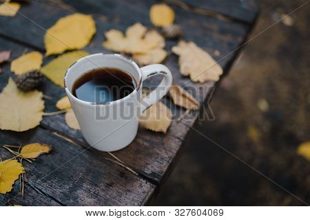On A Old Wooden Table In The Autumn Park Is A Cup With Tea And Coffee, Scattered Yellow Leaves And P
