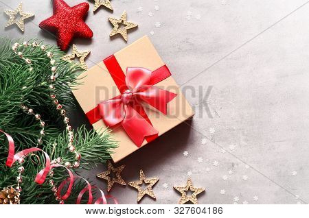 Christmas Background, Green Pine Branches, Cones, Stars And Gift Box On Grey Background. Creative Co