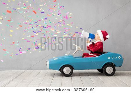 Happy Child Dressed Santa Claus Costume Playing At Home