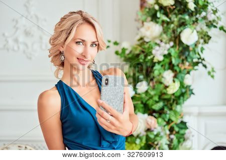 Attractive Young Woman With A Stylish Hairstyle In An Elegant Dress Makes Selfie Posing In The Style