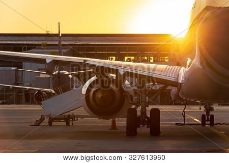 Large Passenger Airliner In The Sunset Against The Background Of The Airport Terminal. Travel By Air