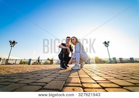 Young Couple Is Posing On A Rock Road. Sitting Together. Girl And Boy Squat Together. Motion Picture