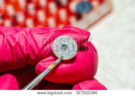 Ophthalmologist Or Surgeon Holds In Hand Dressed In Red Gloves An Eye, Eyeball Prosthesis. Concept P