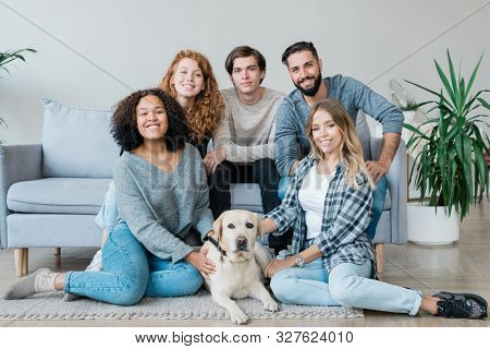 Group of five affectionate teenage guys and girls and white labrador sitting on the floor and on couch in front of camera poster