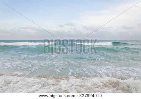 Peaceful beach landscape, the waves arrive and remove the sand from the beach in the subtle beginning of a sunset, the water is an intense turquoise color, the golden sand is guessed through the foam of the shore.