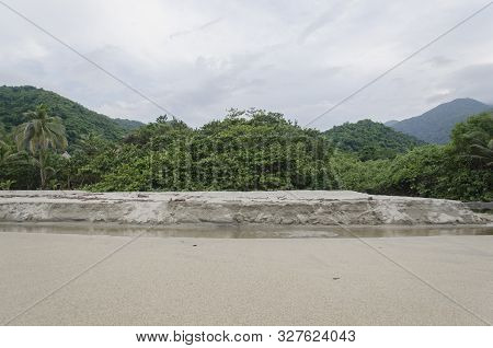 Tayrona National Park beach, a small watercourse flows in the foreground, in the background the majestic tropical forest and the mountains of the Sierra Nevada de Santa Marta