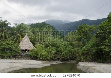 In the foreground, a small watercourse that emerges from the vegetation and flows between the sand reflecting an intense green, a small cabin and the tropical forest. In the background the stunning mountains of Tayrona National Park, Colombia