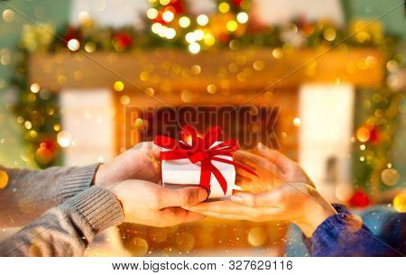 Christmas Gift in hands. Happy Man giving Christmas and New Year Gift box to woman at Home. Family Xmas celebration. Person Holding, Receiving a Gift box. Christmas decoration. Relationship