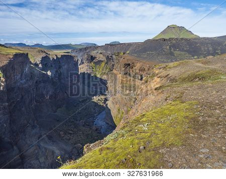 View on majestic Markarfljotsgljufur Canyon gorge and river with green hills and Hattafell mountain near Botnar camp at Fjallabak Nature Reserve in Highlands of Iceland, blue sky background poster