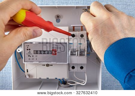An Electrician Installs Of Electrical Panel With Circuit Breakers And An Electricity Meters In A Hou