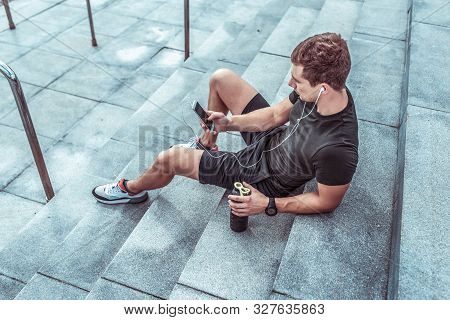Athletic Man Resting In Summer On Steps City. Rest After Workout With Fitness And Outdoor Workout. I