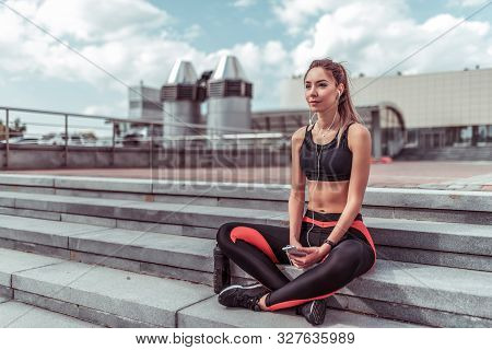 Athlete Woman Resting In Summer On Steps City. Rest After Workout With Fitness And Outdoor Workout.