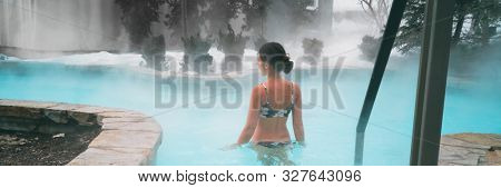Winter wellness spa resort woman swimming in hot spring thermal pools bath at luxury health center panoramic banner background.