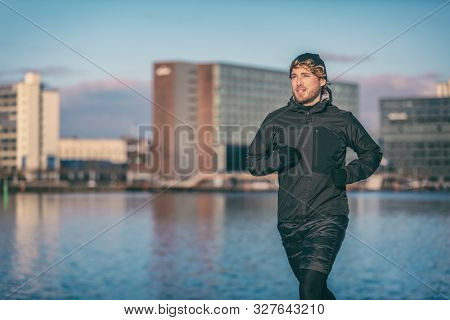 poster of Winter run man jogging outdoor in city harbour running outside wearing cold weather accessories - hat ,gloves , windproof sport jacket. Active fit male athlete.