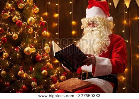 Santa Claus reading book, sitting indoor near decorated xmas tree with lights - Merry Christmas and Happy Holidays!