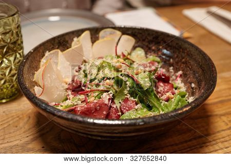 Appetizer with smoked venison, pear and greens in clay table