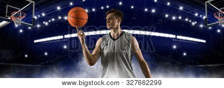 Basketball player spinning a ball on his finger. Floodlit professional sports arena