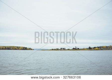 Autumn Landscape With Surface Lake Water, Country Village, Yellow Deciduous And Green Coniferous For