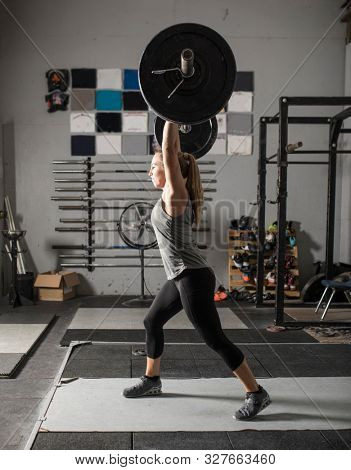 Side view of powerful female weight lifter lifting barbell over her head.