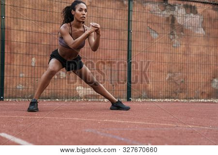 Confident african fitness woman working out at the playground outdoors