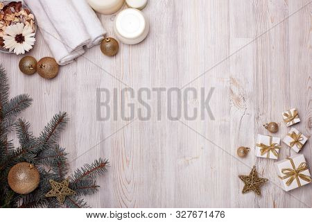 Spa still life with cosmetic creams, towel and Christmas ornaments on light wooden background. Top view with copy space. New Year and Christmas Healthy lifestyle, body care, Spa treatment