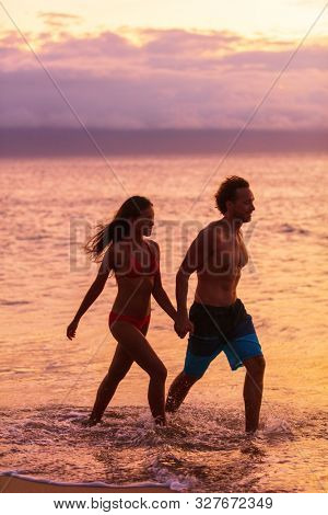 Romantic beach walk silhouette of couple walking relaxing at sunset on tropical summer vacation destination. Travel holidays woman and man stroll outdoor.