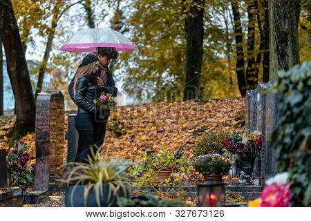Man and woman on a cemetery with flowers and fallen autumn leaves