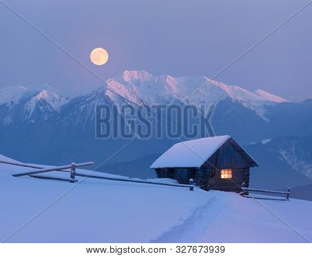 Christmas landscape with a snowy house in the mountains. Fairy night view with full moon. Winter wonderland with footsteps in snow