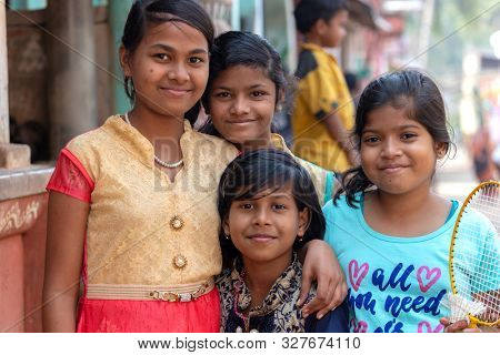 RAGHURAJPUR, INDIA, JANUARY 14, 2019 : Indian smiling girls are posing in the street of Raghurajpur, the handicraft famous village
