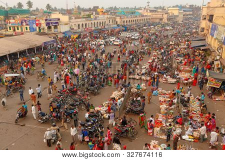 PURI, INDIA, JANUARY 13, 2019 : Perspective point of view of the crowded street market at dusk near the famous Shree Jagannath Temple