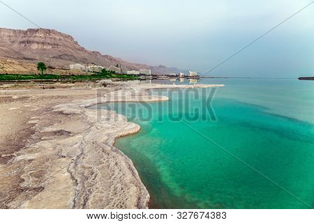 Azure sea water is full of healing salts. Small islets and path of evaporated salt in the water. Early morning at the resorts of the Dead Sea. Israel. Concept of ecological, medical and photo tourism