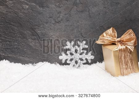 Christmas greeting card. Noel festive background. New year symbol. Gold gift box over snow. Festive background with copy space..