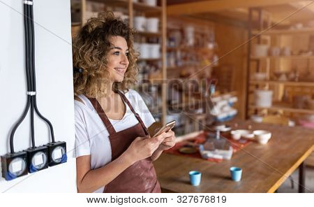Female potter with smartphone in art studio