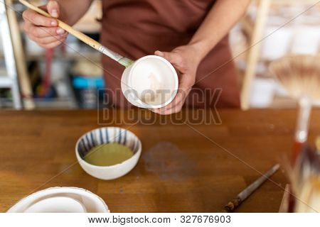 Craftsperson painting a bowl made of clay in art studio