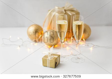 christmas, holidays and celebration concept - two glasses of champagne, gifts and decorations